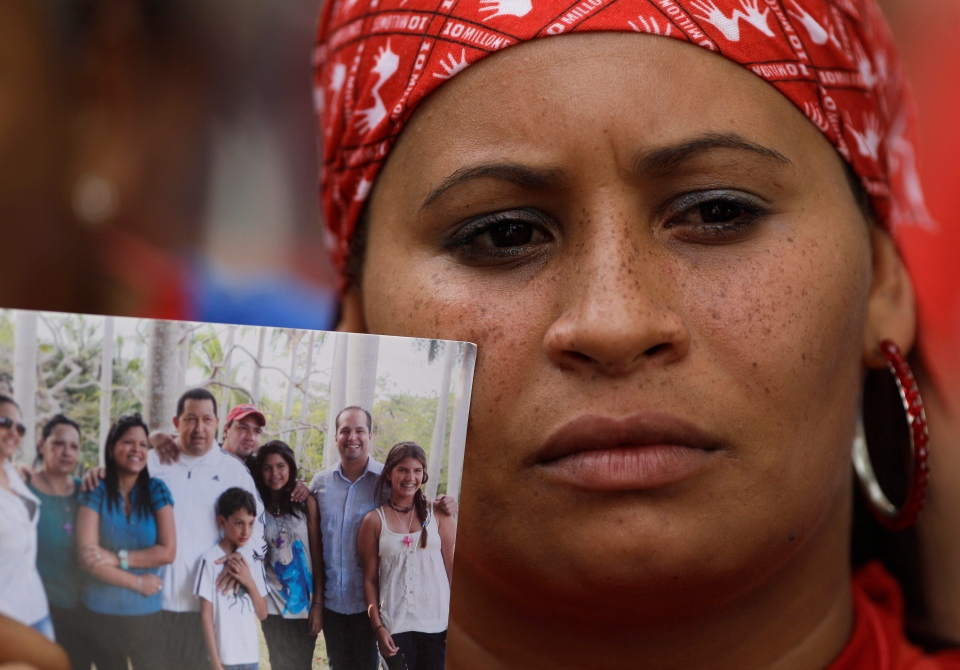 A supporter of Venezuela's President Hugo Chavez holds up a photo of Chavez and his family outside the National Assembly after a session by lawmakers who retained Disodado Cabello as president of the Assembly in Caracas, Venezuela on Saturday, Jan. 5, 2013. (AP Photo / Fernando Llano)