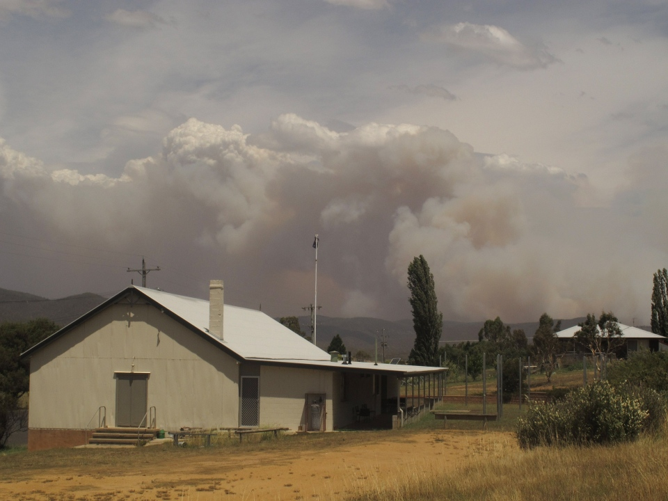Wildfire smoke rises from hills behind the village of Numeralla in New South Wales state on Tuesday, Jan. 8, 2013. (AP / Rod McGuirk)