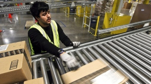 "On ""Cyber Monday,"" Rafael Moreno gets packages ready for shipping at an Amazon.com warehouse in Phoenix on Monday, Nov. 26, 2012. (AP Photo/Ross D. Franklin)"