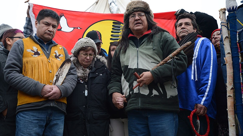 Attawapiskat Chief Theresa Spence stands with fellow hunger strikers Jean Sock, right in blue, Raymond Robinson, second from right in green, and supporter Danny Metatawabin, left, during a press conference outside her teepee on Victoria Island in Ottawa, on Friday, Jan. 4, 2013. (Sean Kilpatrick / THE CANADIAN PRESS)