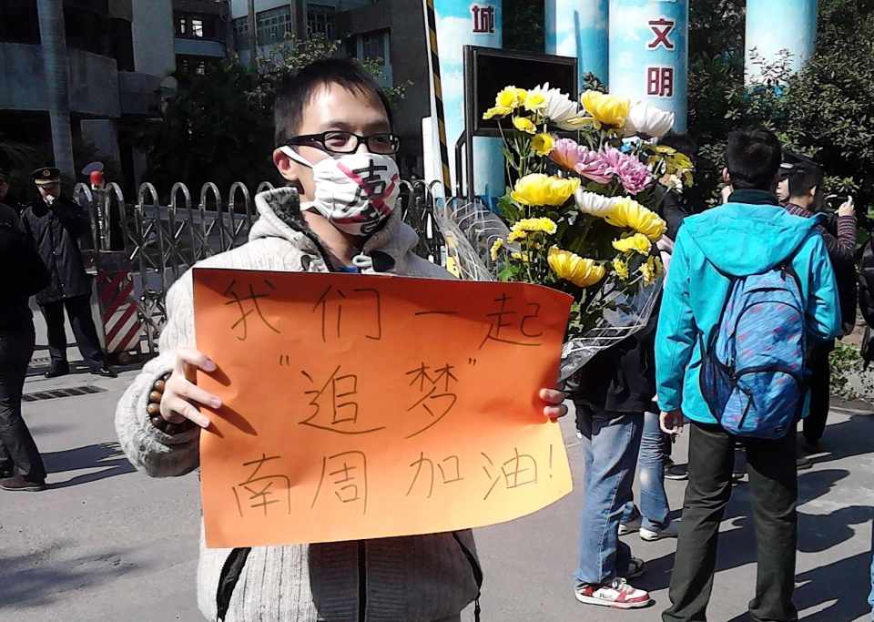 "In this photo taken and provided by activist Wu Wei, a man wearing a mask with words ""Silent"" holds a banner reading: ""Let's chase our dreams together, go Southern Weekly newspaper"" during a protest outside the headquarters of the newspaper in Guangzhou, Guangdong province Monday, Jan. 7, 2013. (AP Photo/Wu Wei)"