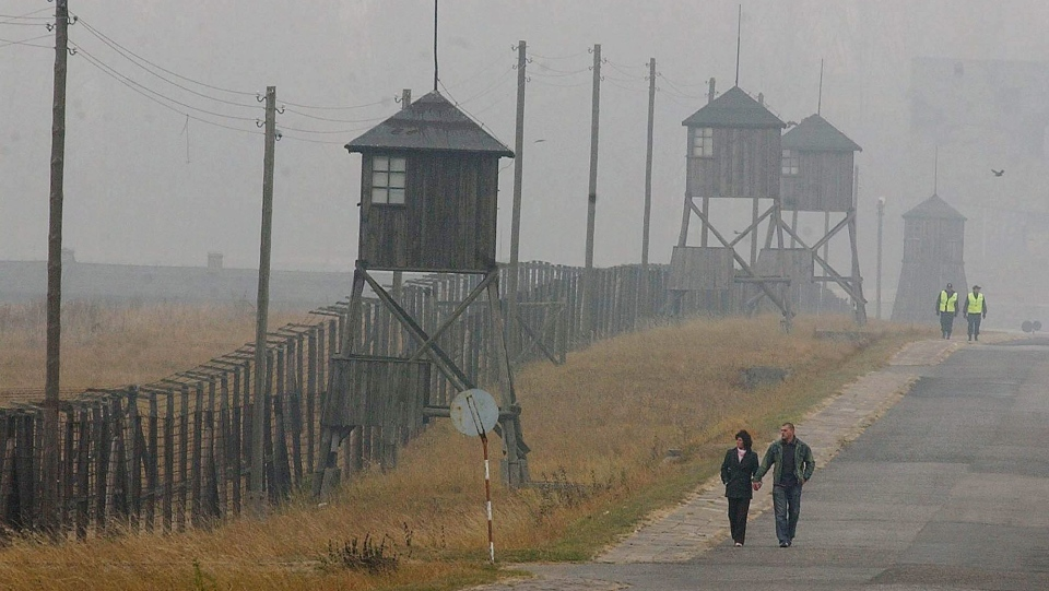 A couple walks along the outer fence of the former Nazi death camp Majdanek outside Lublin in eastern Poland on Wednesday Nov. 9, 2005. Four camp survivors and documentary film makers dug up trinkets and personal items buried by Jews in the spring of 1943 after arriving from the Warsaw ghetto. ( AP Photo/Czarek Sokolowski)