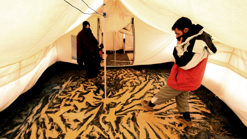 Syrian refugees stand inside their tent after a flood hit Zaatari Syrian refugee camp, near the Syrian border in Mafraq, Jordan, Tuesday, Jan. 8, 2013. (AP / Mohammad Hannon)