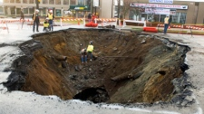 Ciy of Vancouver and Metro Vancouver District officials survey the damage caused by a large sinkhole that developed Sunday on Marine Drive in Vancouver, Monday, Dec. 13, 2010. (CP/Richard Lam)
