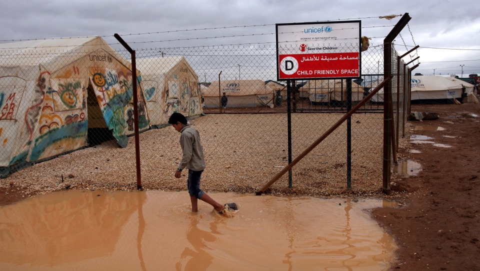 A Syrian refugee boy makes his way through water and mud, next to a UNICEF school at Zaatari Syrian refugee camp, near the Syrian border in Mafraq, Jordan, Tuesday, Jan. 8, 2013. (AP / Mohammad Hannon)
