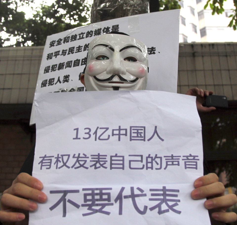 A supporter of Southern Weekly newspaper wears a Guy Fawkes mask while protesting with a banner that reads '1.3 billion Chinese have rights to their own voice and do not want to be represented'' outside the newspaper's headquarters in Guangzhou, in south China's Guangdong province, Tuesday Jan. 8, 2013. (AP Photo)