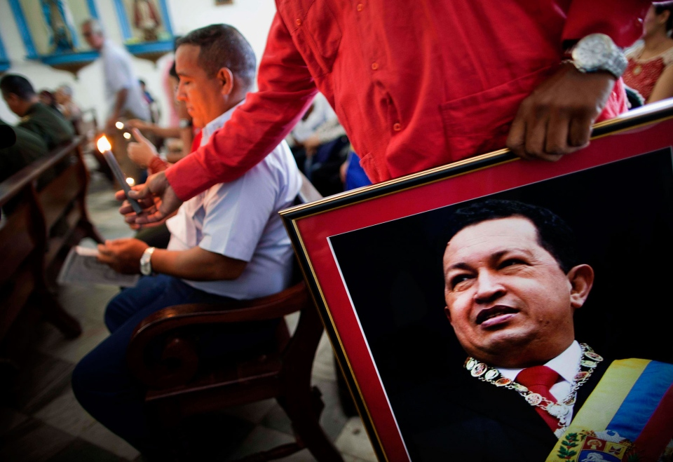 A Venezuelan embassy worker holds a framed image of Venezuela's ailing President Hugo Chavez during the monthly Catholic service devoted to the sick at the Church of Our Lady of Regla, in Regla, across the bay from Havana, Cuba, Tuesday, Jan. 8, 2013. (AP / Ramon Espinosa)