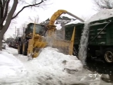 Snow removal equipment is used to remove snow from roads and pathways into trucks for transport in Ottawa on Monday, March 10, 2008.