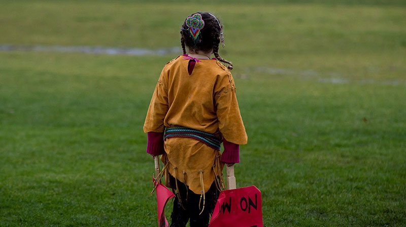 Four-year-old Lily Mervyn, whose mother is Metis and father is of Cherokee heritage, carries signs as she and her family leave after a First Nations Idle No More demonstration at the Douglas-Peace Arch crossing on the Canada-U.S. border near Surrey, B.C., on Saturday, Jan. 5, 2013. (Darryl Dyck / THE CANADIAN PRESS)