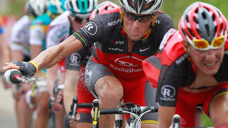 Lance Armstrong throws out his water bottle in the last kilometers of the climb toward Station les Rousses, France, during the seventh stage of the Tour de France cycling race, July 10, 2010. (AP / Bas Czerwinski)