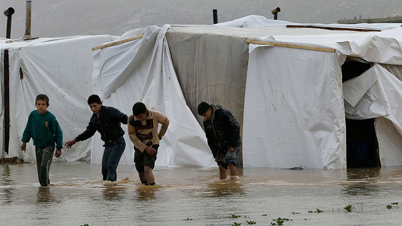 Syrian refugee boys make their way in flooded water at a temporary refugee camp, in the eastern Lebanese Town of Al-Faour near the border with Syria, Lebanon, Tuesday, Jan. 8, 2013. (AP / Hussein Malla)