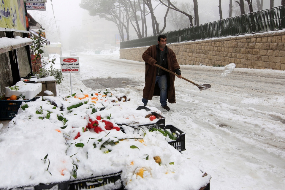A Lebanese man clears snow in front of his shop at the mountain town of Bhamdoun, east of Beirut, Lebanon, Wednesday, Jan. 9, 2013. The fiercest winter storm to hit the Middle East in years has unleashed flash flooding, strong winds and a snowstorm. (AP / Bilal Hussein)