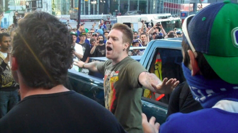 Andrew Perry stands up against a mob of Stanley Cup rioters trying to roll over a pickup truck. June 15, 2011.