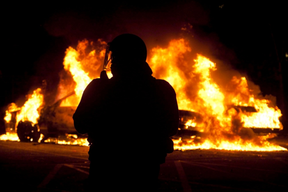 A riot officer watches as two police cars burn during a riot in downtown Vancouver, Wednesday, June 15, 2011. (Ryan Remiorz / THE CANADIAN PRESS)