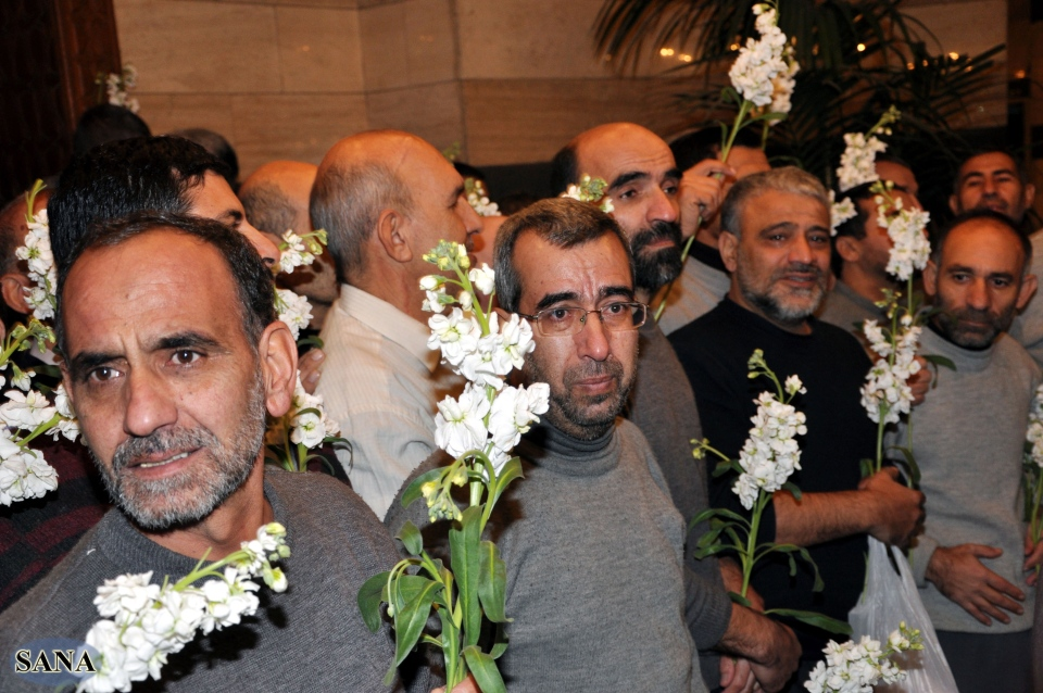 Freed Iranian hostages, who were captured by the Syrian rebels in August, hold roses as they gather at a hotel in Damascus, Syria, Wednesday Jan. 9, 2013. (AP / SANA)