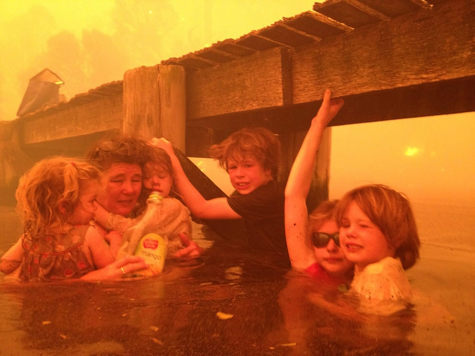 The Holmes family takes refuge under a jetty as a wildfire rages near-by in the Tasmanian town of Dunalley, east of the state capital of Hobart, Australia, Jan. 4, 2013. (AP / Holmes Family, Tim Holmes)