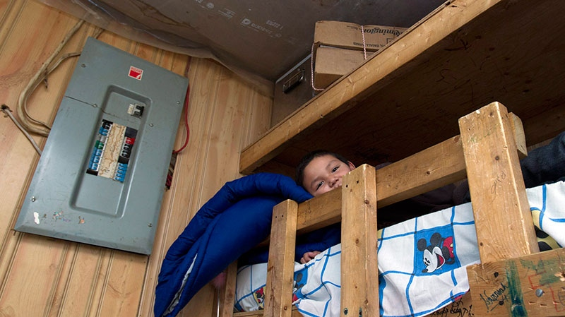 Seven-year-old Ferlin Iahtal lies in his home-made bunk bed in his home in Attawapiskat, Ont., Saturday, Dec. 17, 2011. (Frank Gunn / THE CANADIAN PRESS)
