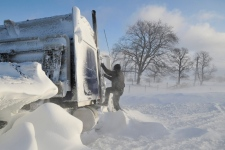 A police officer climbs on the cab of a semi to check on its driver on London Line, east of Sarnia, Ont., Tuesday, Dec. 14, 2010. (Glenn Ogilvie / THE CANADIAN PRESS)