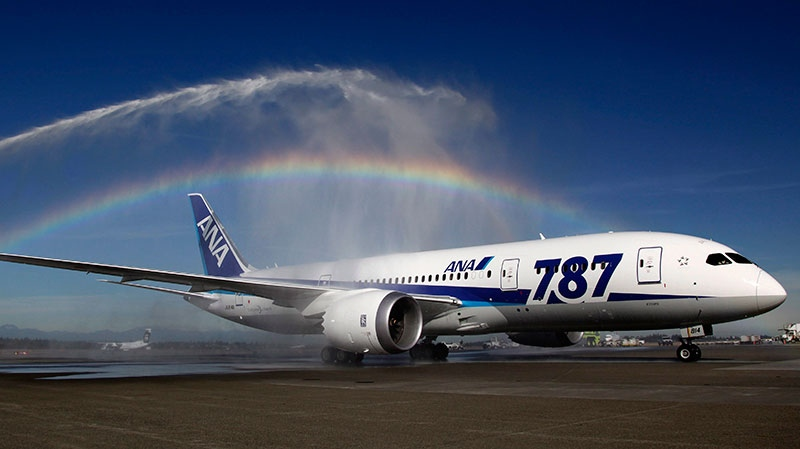 A Boeing 787 operated by All Nippon Airways taxis under a rainbow created by fire trucks at Seattle-Tacoma International Airport in Seattle, Monday, Oct. 1, 2012. (AP Photo/Ted S. Warren)