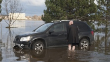 Gary MacDonald wades through a flooded parking lot to get to his vehicle near the St. John River on Tuesday, December 14, 2010 in Fredericton. (THE CANADIAN PRESS/David Smith)