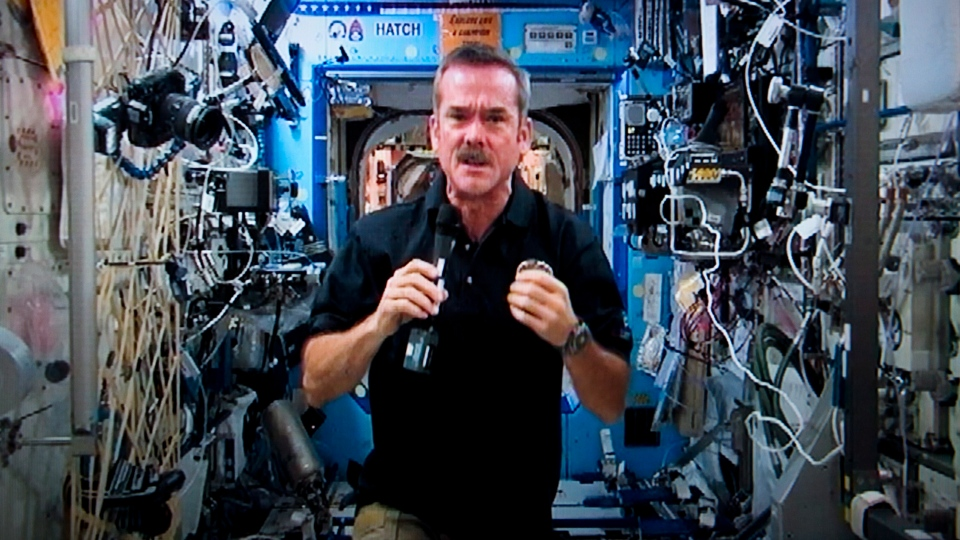 Canadian astronaut Chris Hadfield responds to a question during a news conference from the International Space Station on a photograph taken from a television monitor on Jan. 10, 2013. (Paul Chiasson / THE CANADIAN PRESS)
