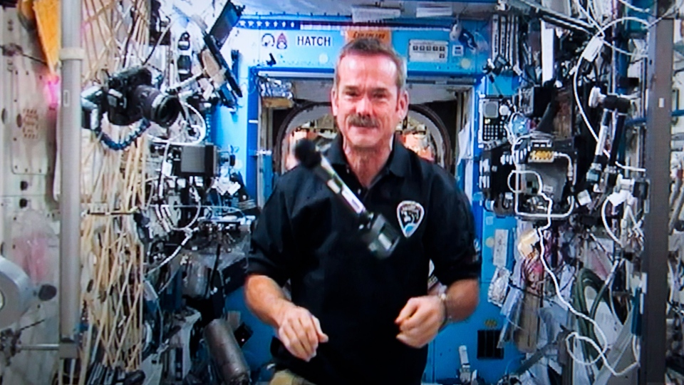 Canadian Astronaut Chris Hadfield lets his microphone float mid-air at the end of a news conference from the International Space Station on a photograph taken from a television monitor Thursday, January 10, 2013. (Paul Chiasson / THE CANADIAN PRESS)