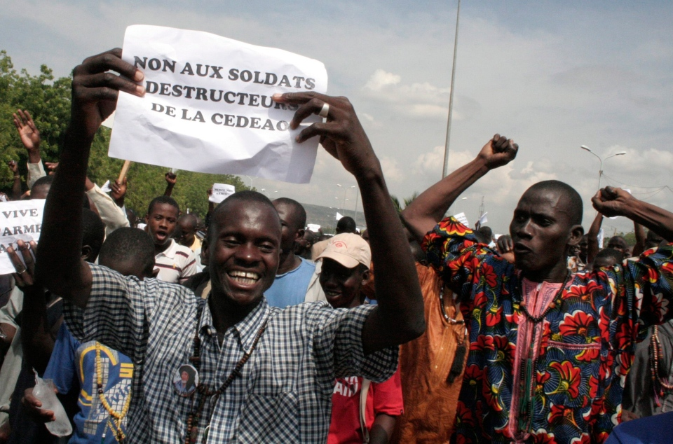 """A man carryies a sign reading """"No to the destructive soldiers of ECOWAS"""" as Malians opposed to a military intervention to retake Mali's Islamist-controlled north march in the streets of the capital, Bamako, Mali, Thursday, Oct. 18, 2012. (AP / Harouna Traore)"""