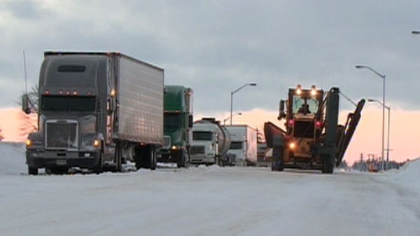 A snow plough passes a line of stranded tractor trailer's left abandoned along a stretch of Highway 402, Wednesday, Dec. 15, 2010.