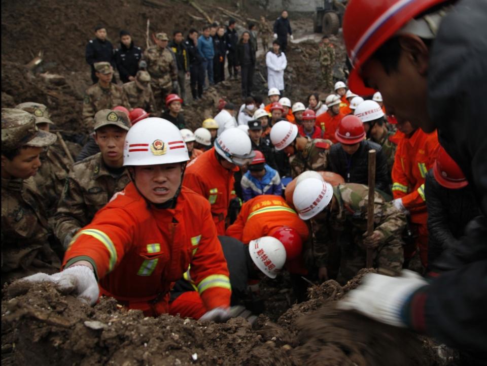Rescuers work at the mud-inundated debris after a landslide hit Zhaojiagou in Zhenxiong County, southwest China's Yunnan Province,  Jan. 11, 2013. (AP / Xinhua Zhang Guangyu)