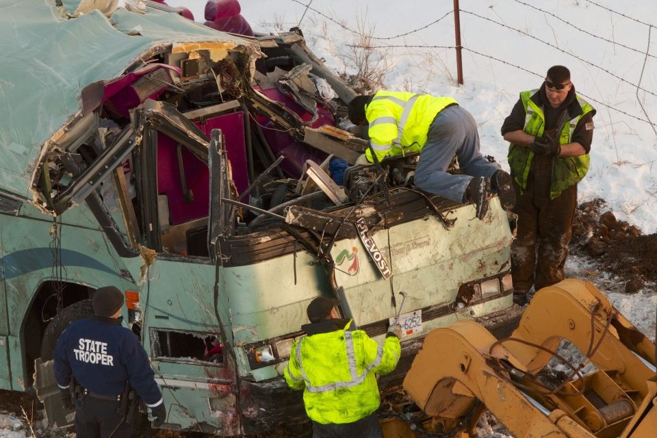 Workmen move a bus that plummeted 200 feet down an embankment in rural Eastern Oregon on Sunday, killing nine and sending multiple to hospitals, Monday, Dec. 31, 2012. (The Oregonian, Randy L. Rasmussen)