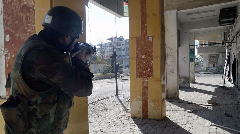 A Syrian soldier aims his rifle at free Syrian Army fighters during clashes in the Damascus suburb of Daraya, Syria, Sunday, Dec. 2, 2012. (SANA)