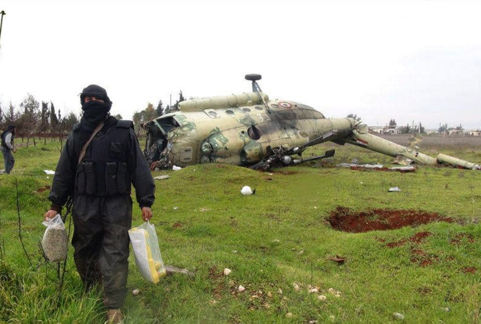 A Syrian rebel carries food supplies as he walks in front of a damaged helicopter at Taftanaz air base that was captured by the rebels, in Idlib province, northern Syria on Friday, Jan. 11, 2013. (AP / Edlib News Network ENN)