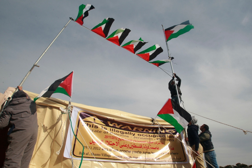 Palestinian activists place Palestinian flags in the new 'outpost ' of Bab al-Shams (Gate of the Sun) in an area known as E1, near Jerusalem, Saturday, Jan 12, 2013. (AP / Nasser Shiyoukhi)
