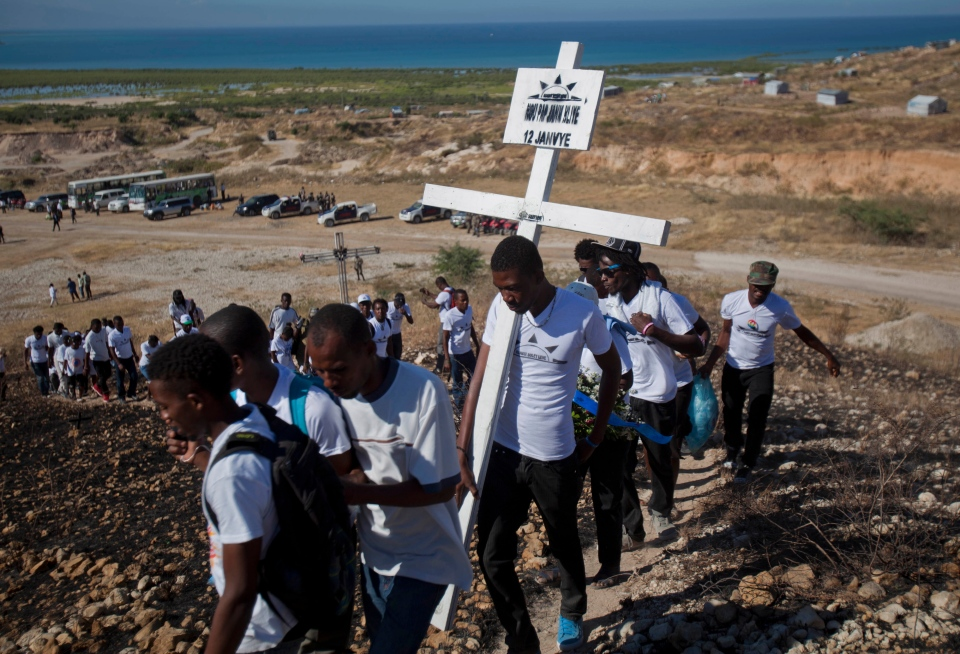 Relatives of those who died in the 2010 earthquake walk in single file to place a cross on a hilltop to remember those who died in the devastating earthquake, prior to a memorial service at Titanyen, a mass burial site north of Port-au-Prince, Haiti, Saturday, Jan. 12, 2013. (AP / Dieu Nalio Chery)