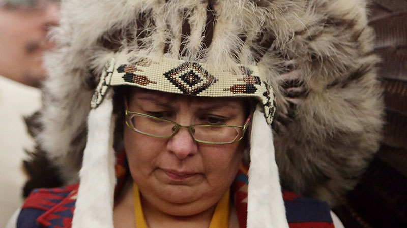 Attawapiskat Chief Theresa Spence, wearing a headdress, takes part in a drum ceremony before departing a Ottawa hotel to attend a ceremonial meeting at Rideau Hall with Gov. Gen. David Johnston in Ottawa, Friday, Jan. 11, 2013. (Fred Chartrand / THE CANADIAN PRESS)