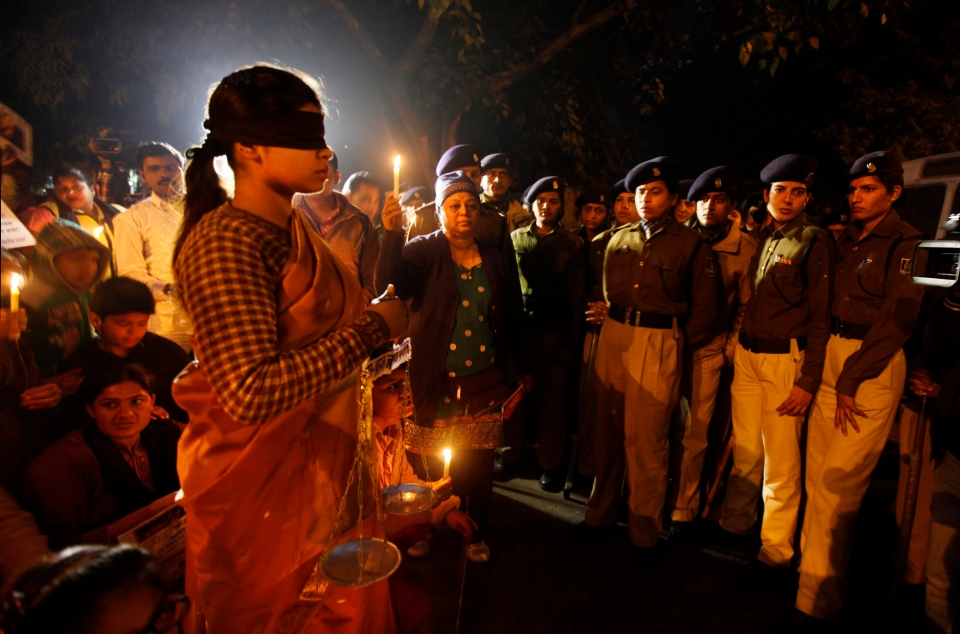 An Indian girl, left, dressed as Lady Justice stands after the participants of a candlelight vigil were stopped by Indian police in New Delhi, India, Sunday, Jan. 13, 2013. (AP / Altaf Qadri)