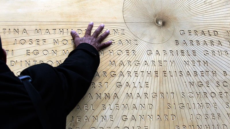 A relative of the Costa Concordia shipwreck's victims touches a commemorative plaque bearing the names of the 32 people who lost their lives in the disaster, in the Tuscan island Isola del Giglio, Italy, Sunday, Jan. 13, 2013.  (AP / Gregorio Borgia)