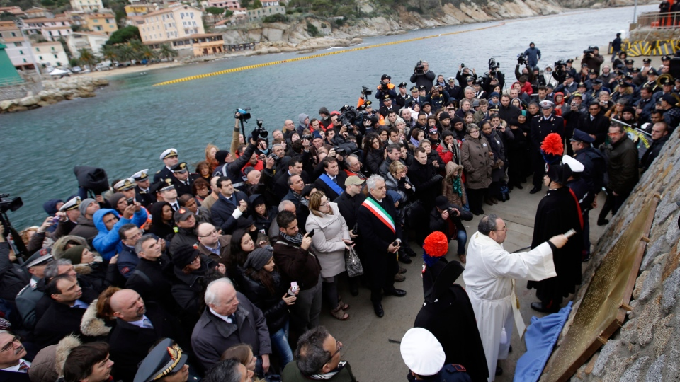 A priest blesses a commemorative plaque bearing the names of the 32 people who died in the Costa Concordia shipwreck, after it was unveiled in the Tuscan island Isola del Giglio, Italy, Sunday, Jan. 13, 2013. (AP / Gregorio Borgia)
