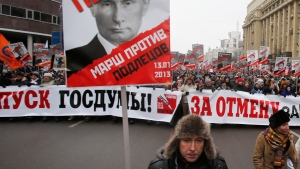"People carry posters of Russian President Vladimir Putin with the words reading ""March Against the Scum and Shame"" during a protest rally in Moscow, Russia, Sunday, Jan. 13, 2013, with the banner reading 'Dissolution of the State Duma'. (AP / Misha Japaridze)"