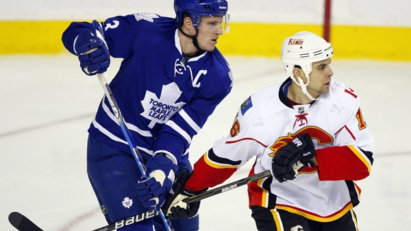 Toronto Maple Leafs' Dion Phaneuf, left, battles with Calgary Flames' Tom Kostopoulos during first period NHL hockey action in Calgary, Alta., Thursday, Dec. 16, 2010. (THE CANADIAN PRESS/Jeff McIntosh)