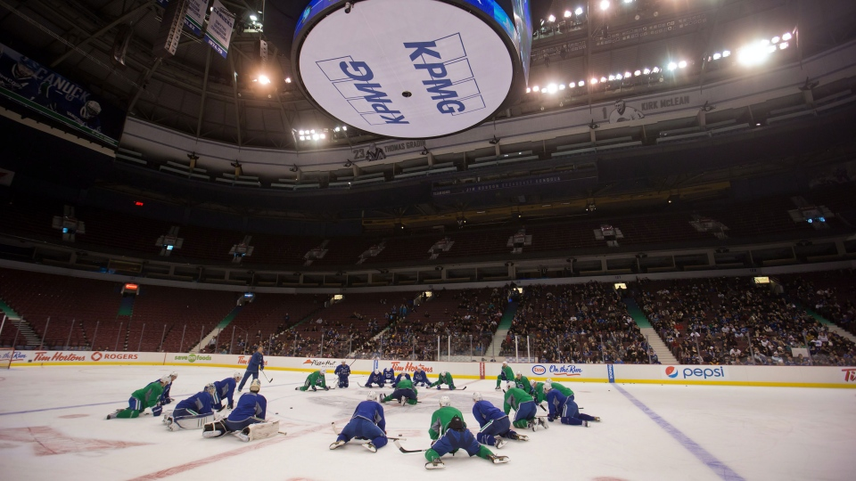 Vancouver Canucks players stretch as a few hundred fans watch during practice on the first day of the NHL hockey team's training camp in Vancouver, B.C., on Sunday January 13, 2013. (Darryl Dyck / THE CANADIAN PRESS)