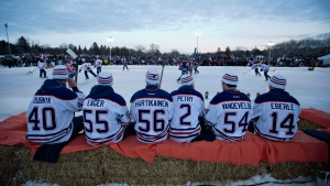 Edmonton Oilers sit on bales of hay as they wait their turn to play in an game of outdoor shinny after the Oilers first day of NHL training camp in Edmonton, Alta., on Sunday January 13, 2013. (Jason Franson / THE CANADIAN PRESS)