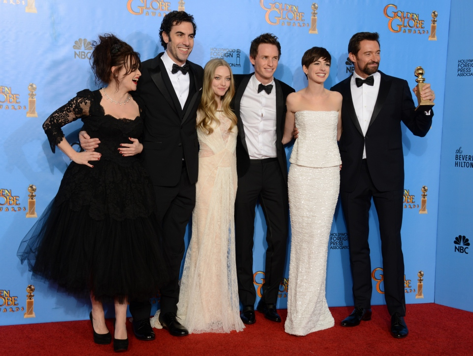 Actors, from left, Helena Bonham Carter, Sacha Baron Cohen, Amanda Seyfried, Eddie Redmayne, Anne Hathaway and Hugh Jackman pose with the award for best motion picture comedy or musical for 'Les Miserables' backstage at the 70th Annual Golden Globe Awards at the Beverly Hilton Hotel in Beverly Hills, Calif., Sunday Jan. 13, 2013. (Jordan Strauss / Invision)