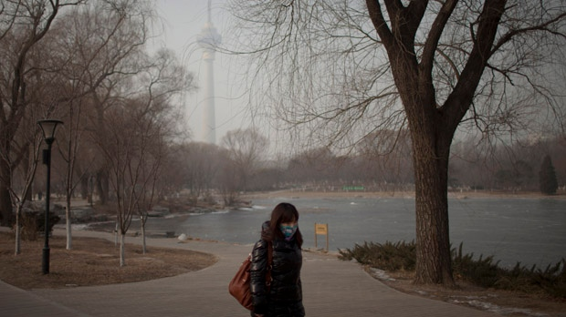 A woman wears a mask while walking in a park near the China Central Television Tower, background, on a hazy day in Beijing, China on Monday, Jan. 14, 2013. (AP / Alexander F. Yuan)