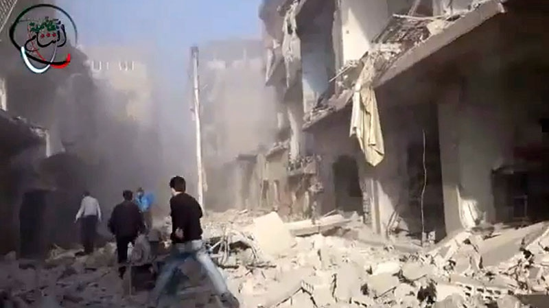 In this photo taken from video obtained from the Shaam News Network, which has been authenticated based on its contents and other AP reporting, Syrian men run to aid injured people in the aftermath of a strike by Syrian government warplanes on the residential neighborhood of Maadamiyeh south of Damascus, Syria, Monday, Jan. 14, 2013. (AP / Shaam News Network via AP video)