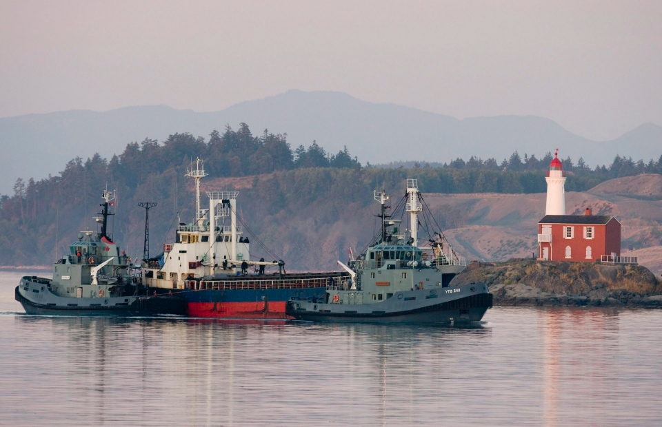 The MV Sun Sea is escorted past Fisgard Lighthouse and into CFB Esquimalt in Colwood, B.C., on Friday, Aug. 13, 2010. (Jonathan Hayward / THE CANADIAN PRESS)