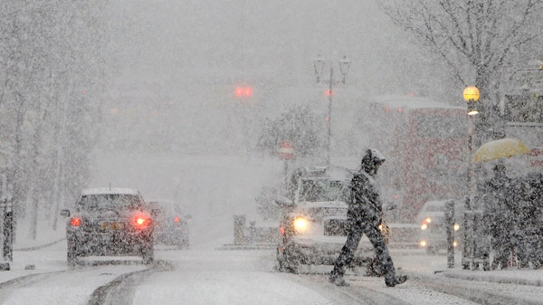 A pedestrian crosses a road during a snow fall in central London, Saturday, Dec. 18, 2010. (AP / Alastair Grant)