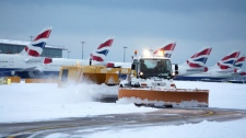 A snow plough clears the taxi ways after heavy snowfall at Heathrow Airport, London, Saturday Dec. 18, 2010. (AP / PA, Steve Parsons)