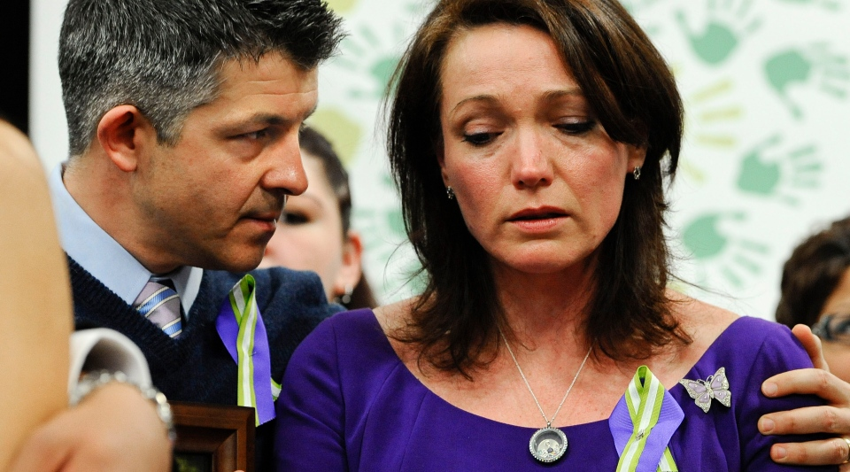 Ian and Nicole Hockley, parents of Sandy Hook School shooting victim Dylan, listen at a news conference at Edmond Town Hall in Newtown, Conn., Monday, Jan. 14, 2013. One month after the mass school shooting at Sandy Hook Elementary School, the parents joined a grassroots initiative called Sandy Hook Promise to support solutions for a safer community. (AP Photo / Jessica Hill)
