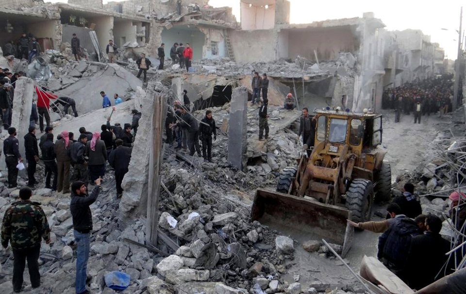 People gather around destroyed buildings after airstrikes hit parts of Aleppo, Syria, Monday, Jan. 14, 2013. (Aleppo Media Center AMC)